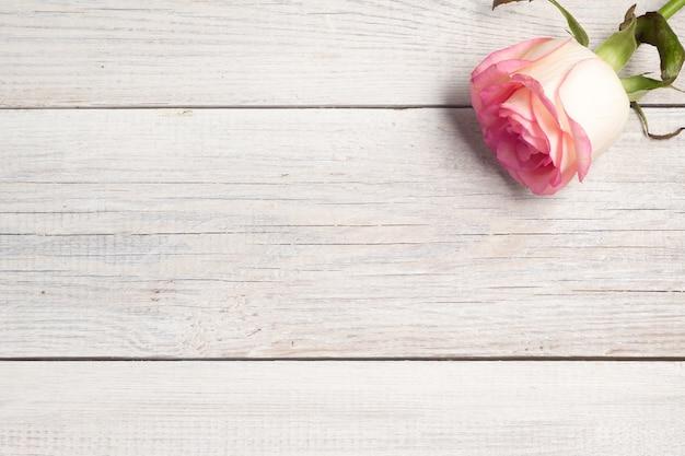 白い木製のヴィンテージの背景にピンクのバラ。
