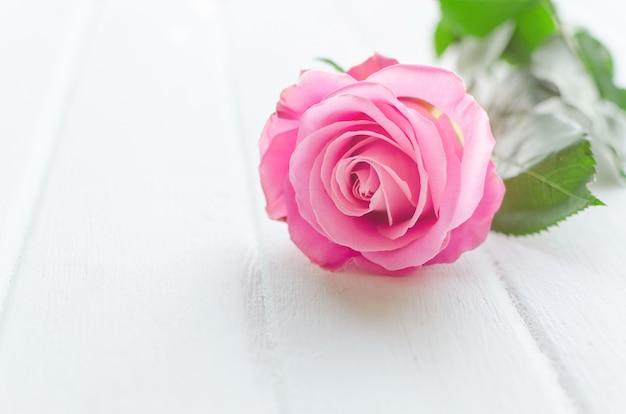 白い木の板にピンクのバラ。母のまたはバレンタインの