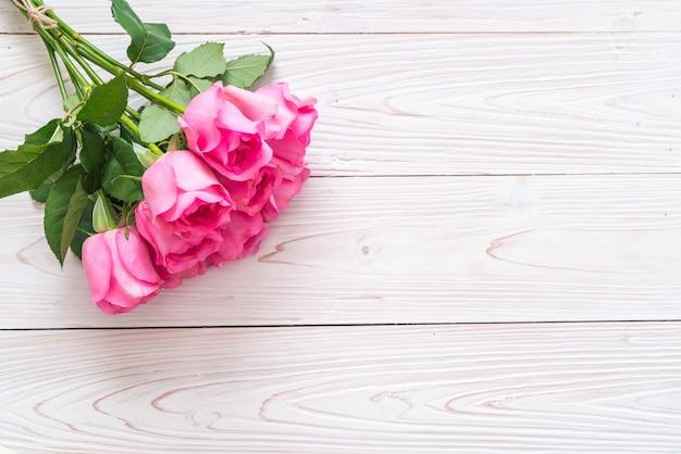 Pink rose in vase on wood background