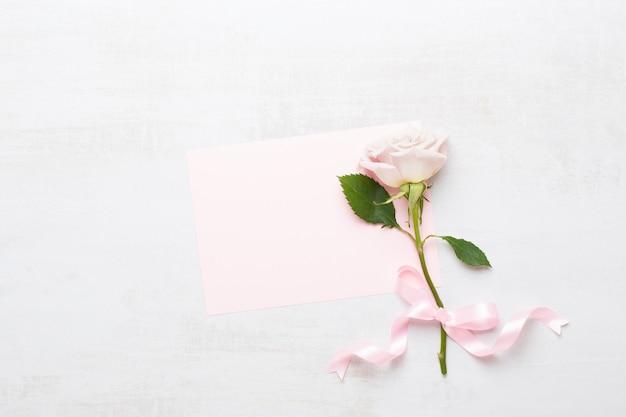 灰色の背景に空白のグリーティングカードとピンクのバラ。フラットレイ、上面図