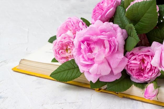 ピンクのバラと明るい石の表面に黄色の表紙の本
