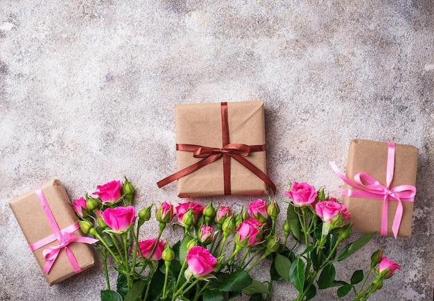 Розовые розы и подарочные коробки с лентами Premium Фотографии