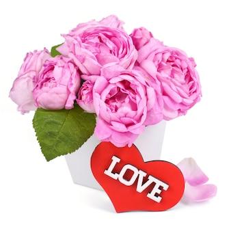 ピンクのバラと木製の机の上の花びらと白い背景で隔離の言葉の愛と赤い木製のハートの形。バレンタインデーの背景。