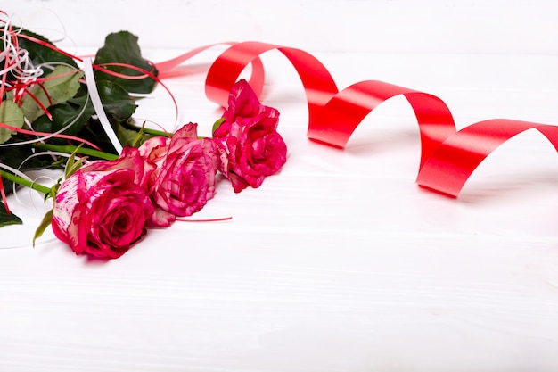 ピンクのバラと白い背景で隔離の赤いリボン