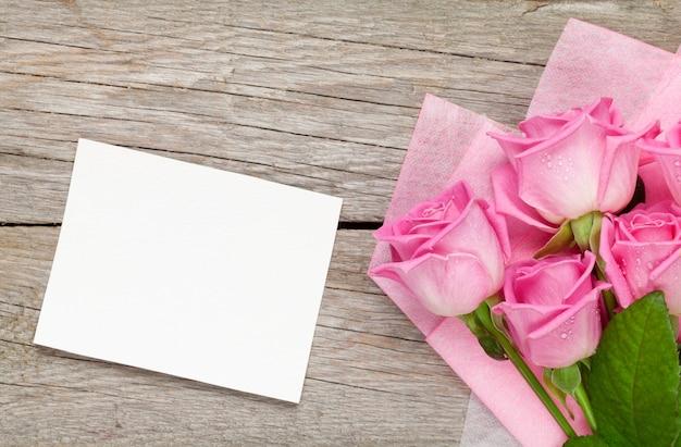 Букет розовых роз и пустая открытка за деревянным столом