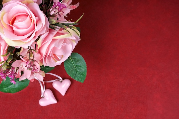 ピンクのバラの花束と赤い背景の上のバレンタインデーの心。上面図、コピースペース付きフラットレイ