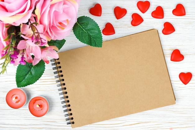 ピンクのバラの花束と白い木製の背景に紙のメモ帳とキャンドルとバレンタインデーの心。上面図、コピースペース付きフラットレイ