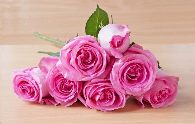 木製のテーブルにピンクのバラの花束