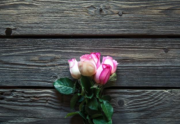 나무 테이블 위에 핑크 장미 꽃다발입니다. 복사 공간이있는 상위 뷰. 꽃들