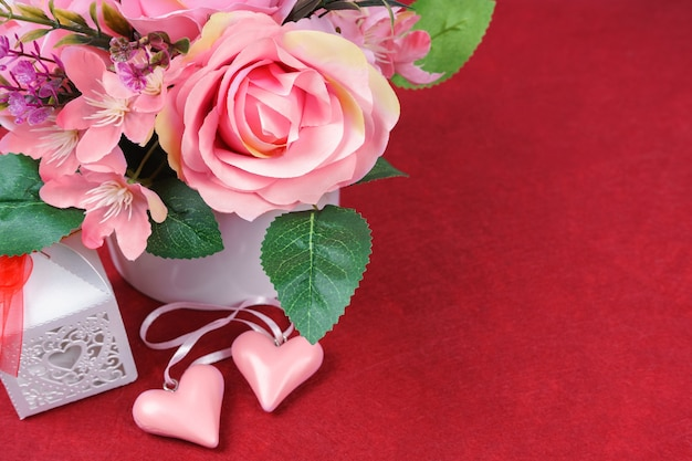 Pink roses bouquet and valentine's day hearts on red background. top view, flat lay with copy space