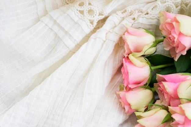 Pink roses bouquet on wedding dress background