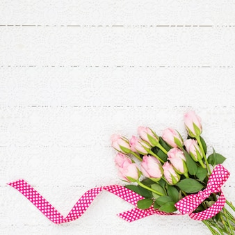 Pink roses bouquet on white tablecloth