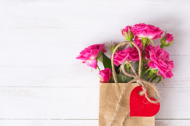 Pink roses on craft paper bag with red paper heart on wooden white background