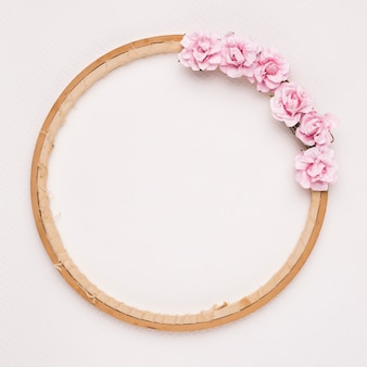 Pink roses decorated on circular wooden frame against white backdrop