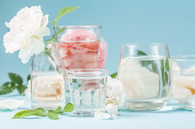 ガラスの液体の水で歪んだピンクのバラ