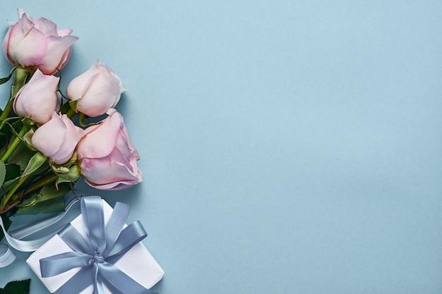 Букет цветов розовых роз с лентой, подарочной коробкой и пасхальными яйцами на красивом синем фоне. шаблон поздравительной открытки с копией пространства