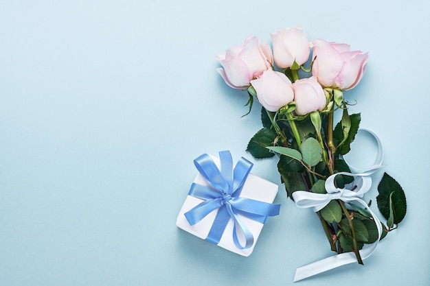 Pink roses flowers bouquet with ribbon and gift box over beautiful blue background. greeting card template with copy space