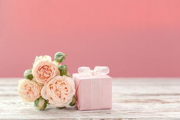 Pink roses flowers and gift or present box pink background.