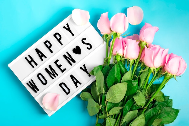 Pink roses flowers and lightbox with quote happy womens day on blue background flat lay