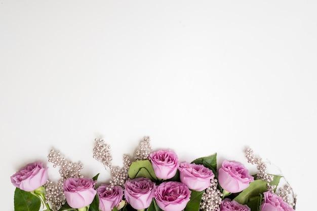銀のビーズの装飾が施された白い背景の上にピンクのバラの花。エレガントな女性や母の日の背景。コピースペースの概念