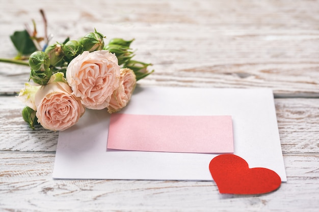Pink roses flowers with gift card and red paper heart on pink