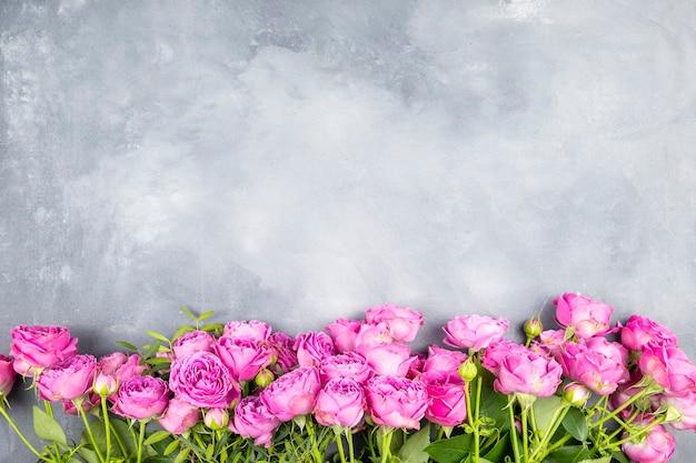Рамка из розовых роз на сером мраморе