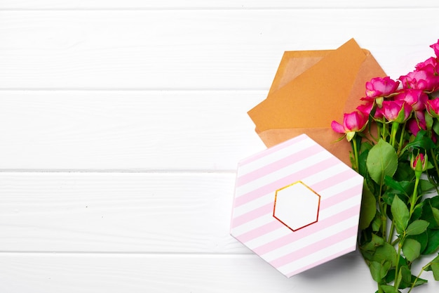 Pink roses and gift box top view copy space