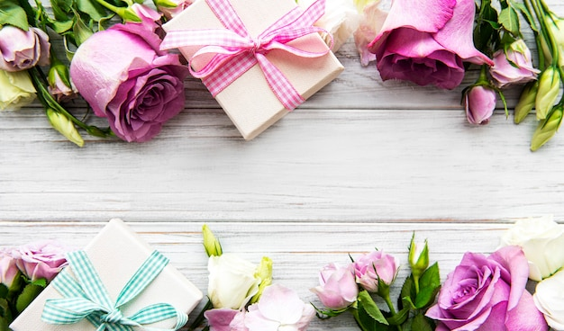 Pink roses and gift boxes on white wooden background