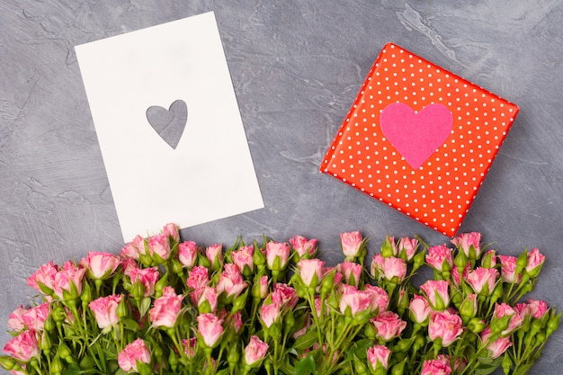Pink roses, gift in red box and card with heart on grey background woman's day mother's st. valentine's day concept