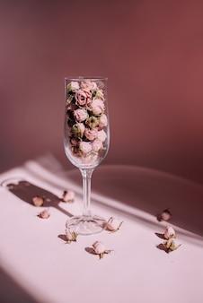 Розовые розы в стакане на розовом