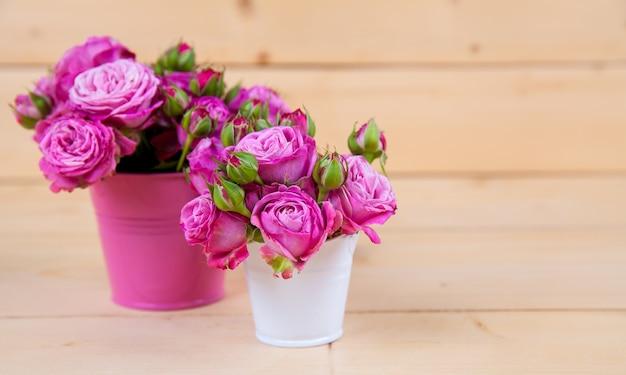 木製の背景と花瓶にピンクのバラ