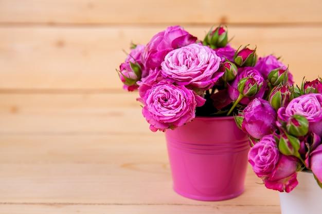 木製の背景に花瓶のピンクのバラ。バレンタインデー、バレンタイン