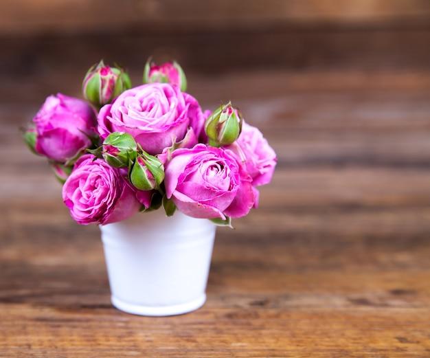 木の表面の上に花瓶にピンクのバラ