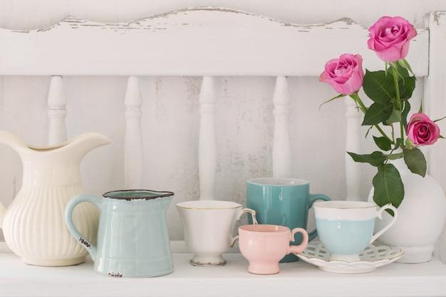 Розовые розы в вазе и посуда на белой деревянной полке