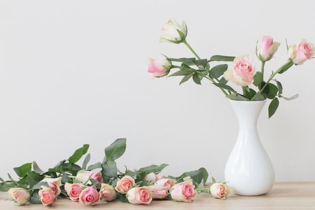 白いテーブルの上に花瓶のピンクのバラ