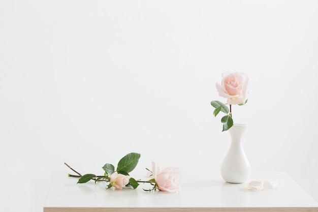 白い背景の上の白い花瓶のピンクのバラ