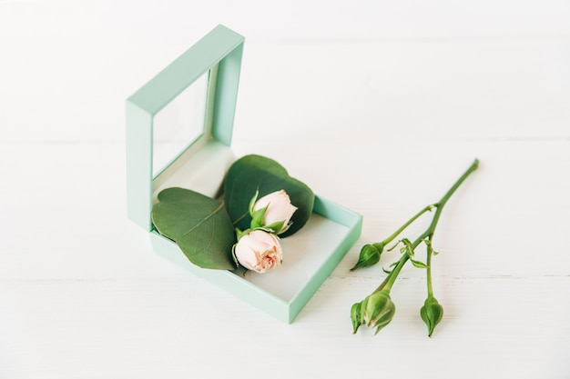 Pink roses inside a mint gift box on white wooden background