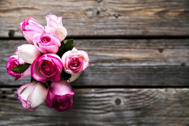 木製のテーブルにピンクのバラ。ビンテージ