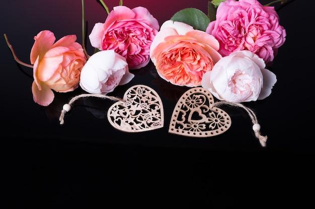 Розовые розы на черном фоне. композиция цветов. рама из романтической розовой розы на черном фоне. плоская планировка