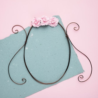 분홍색 배경 위에 종이에 빈 금속 프레임에 핑크 장미
