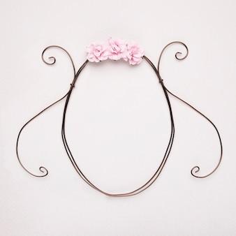 白い背景に対して空の楕円形フレームにピンクのバラ