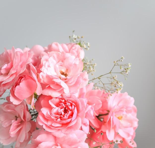 背景のグリーティングカードや結婚式の招待状に最適な灰色の背景にピンクのバラ