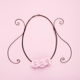 Розовые розы на овальной раме на розовой стене