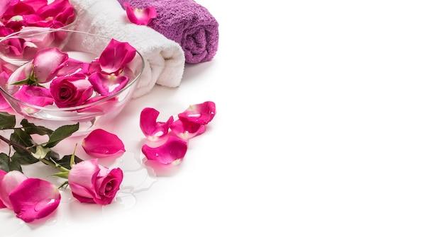 Лепестки розовых роз в шаре с полотенцами и чистой водой над белой .. концепция спа и оздоровления.
