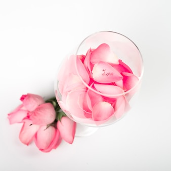 Pink roses petals in glass on table