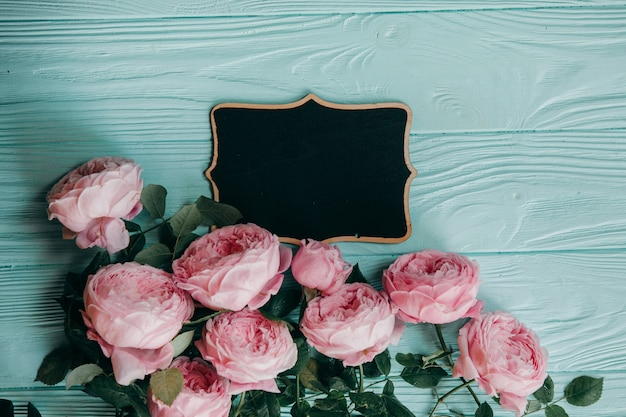 Pink roses and a picture frame on a blue table