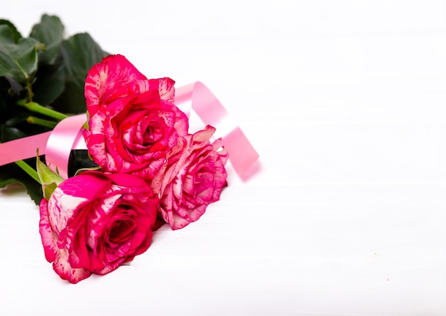 Pink roses and red ribbon isolated on white background