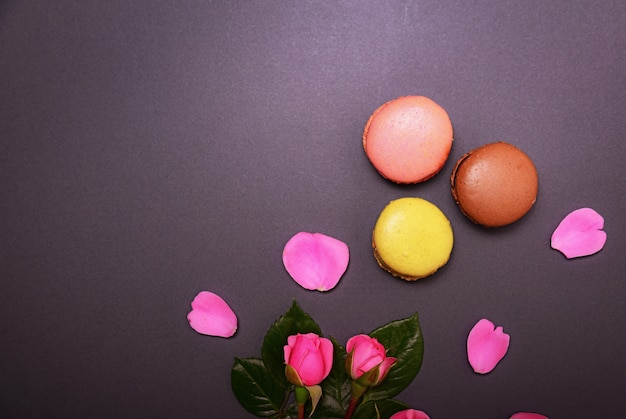 Pink roses and three multicolored macaroons