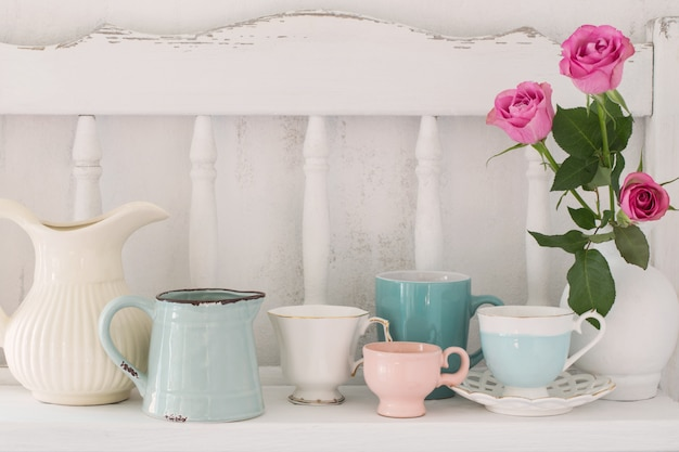 Pink roses in vase and dinnerware on white wooden shelf