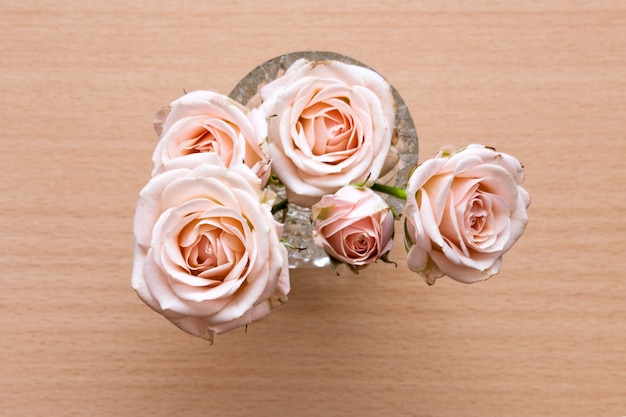 Pink roses in a vase on a wooden desk